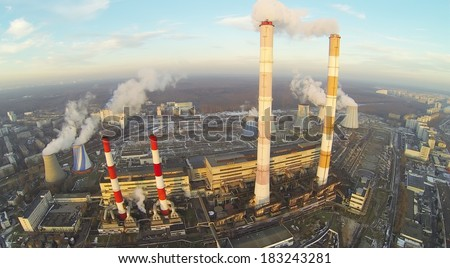 Power plant with many different chimneys at  sunnywinter day. Aerial view - stock photo