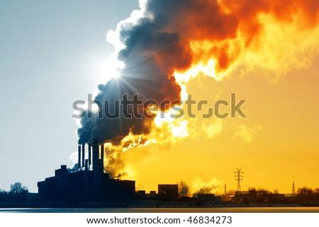 Power plant with orange smoke - stock photo