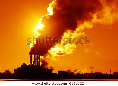 Power plant with smoke and dirty orange air - stock photo