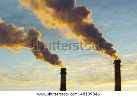 Power plant with smoke under sky