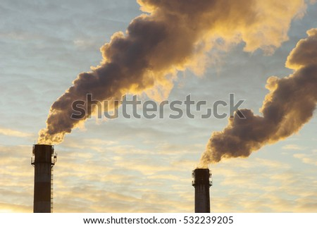 Power plant with smoke under sunset