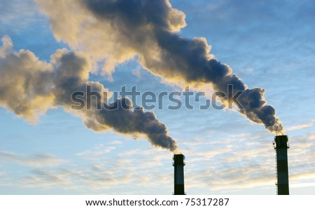 Power plant with smoke under sunset - stock photo
