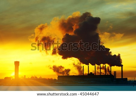 Power plant with smoke under sunset light