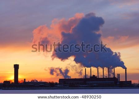 Power plant with smoke under sunset light - stock photo