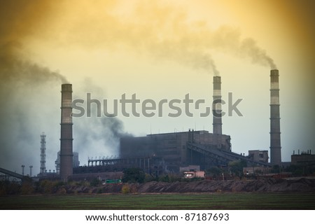 Power plant with yellow smoke - stock photo
