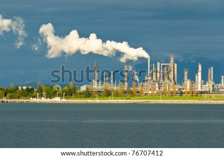 Power plants generating smokes at the sunset - stock photo