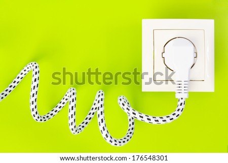 Power plug gets green energy from power socket against bright green background - stock photo