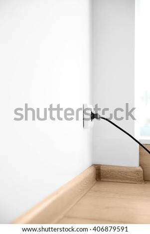 Power plug into power outlet indoors - stock photo