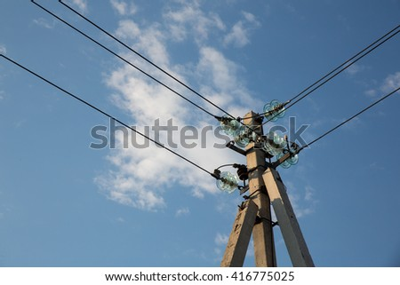 Power pole with electrical insulators against the sky - stock photo