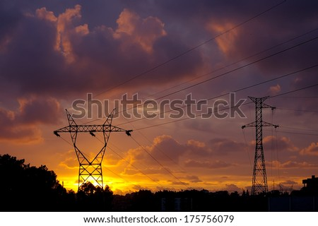 Power pylons in front of a fantastic sunset sky. - stock photo