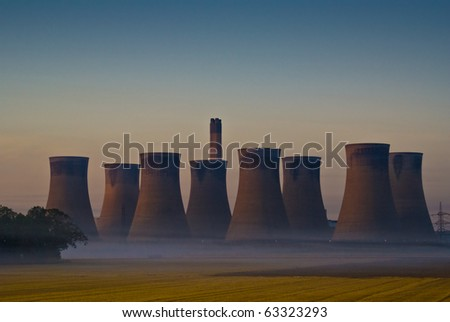 Power Station in the early morning with mist on the fields - stock photo