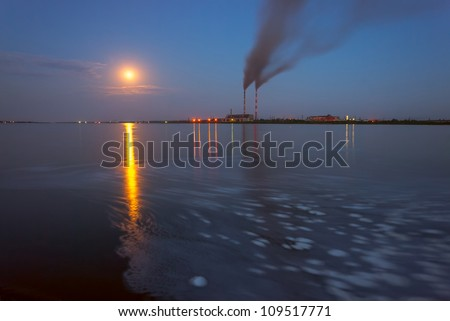 Power station in the evening, with lights and smoke reflection in water, full moon, long exposure - stock photo
