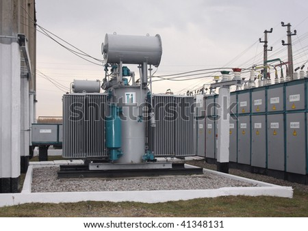 Power transformer in a distribution substation separated from another one by a wall - stock photo