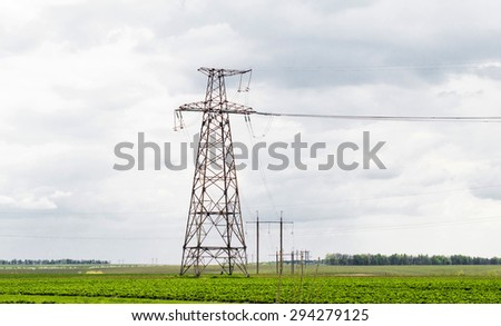power transmission lines against the sky and green field