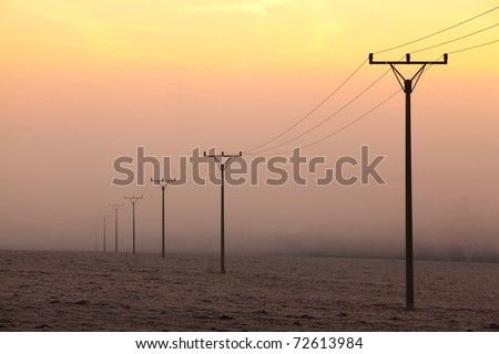 Power-transmission poles in the mist in winter nature - stock photo