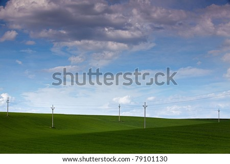 Power-transmission poles on the empty barley field in spring - stock photo