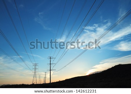 Power transmission pylons silhouetted against a blue and orange sky