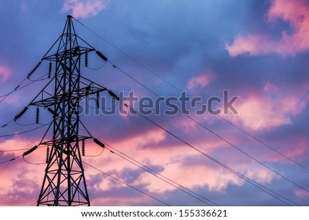 Power Transmission tower against a blue and pink sunset glowing in the background.