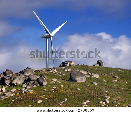 Power windmill next to a mountain shack.