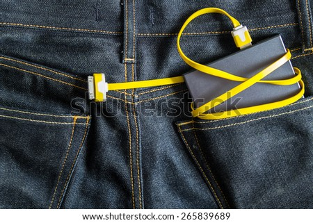 powerbank in jeans pocket , Battery Charger , Technology in everyday life ,electric energy in jeans - stock photo