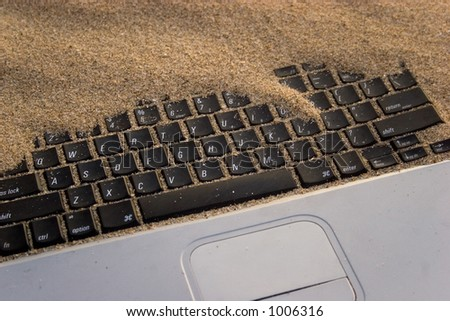 Powerbook notebook computer almost covered in sand.