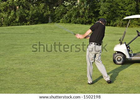 Powerful approach shot from the fairway.  Club motion blur. - stock photo