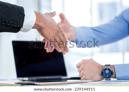 Powerful business handshake. Close-up view of a handshake while two successful businessman shaking hands at the table against each in the business office in formal wear and work at a laptop.