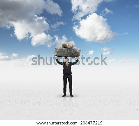 Powerful businessman holding a huge stone above the head. Cloudy sky background.