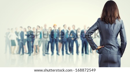 Powerful businesswoman standing with back with business team at background - stock photo