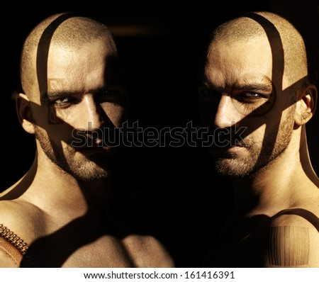 Powerful fine art portrait of two twin male models in darkness with shadows and abstract elements obscuring their faces - stock photo