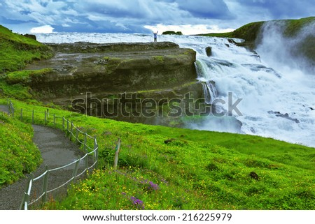 Powerful high-water waterfall in Iceland. For walks and observations on the hillside laid convenient path - stock photo