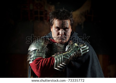 Powerful knight in the armor and iron glove. Dark background. - stock photo