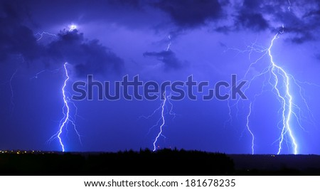 Powerful lightning over the field - stock photo