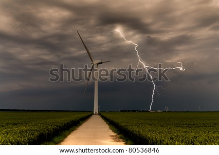 Powerful lightning strikes wind turbine in the afternoon - stock photo