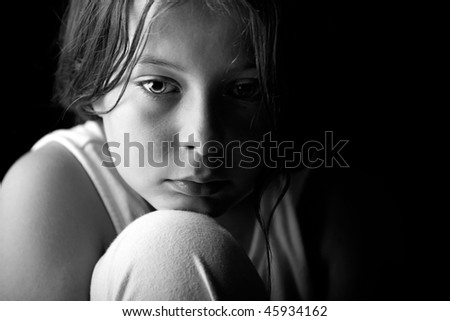 Powerful Low Key Shot of a Young Child Looking Sad - stock photo
