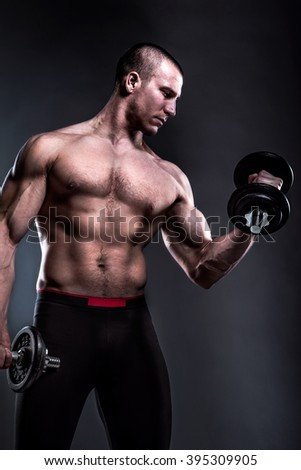 powerful man holding dumbbells low key