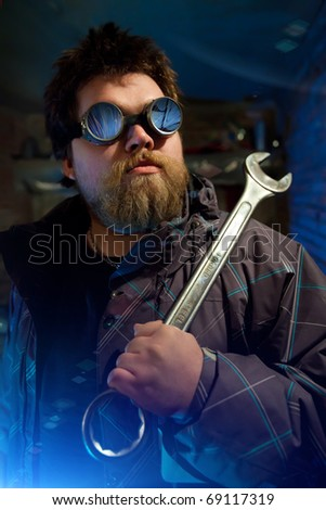 Powerful mechanic with the big wrench on the repair station background - stock photo