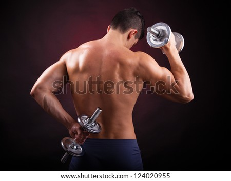 Powerful muscular man lifting weights on black background - stock photo