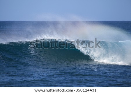 powerful ocean waves with rainbow crest foam breaking by the shores of Gran Canaria - stock photo