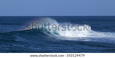 powerful ocean waves with rainbow plume breaking by the shores of Gran Canaria - stock photo
