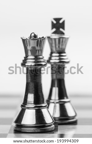 Powerful Queen - Rugged brass chess queen and king pieces on a chess board. Shallow DOF used for emphasis of powerful queen.