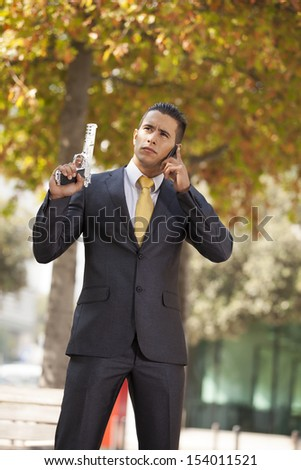 Powerful security businessman aiming a gun and calling at the cellular - stock photo