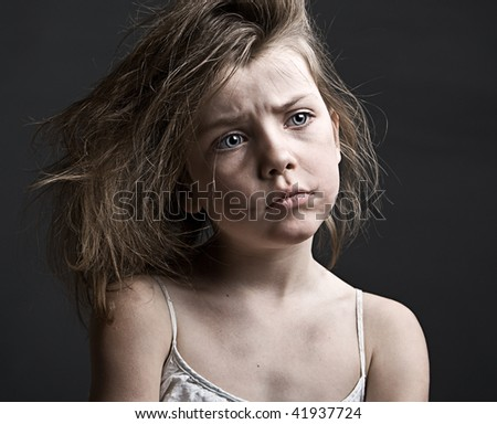 Powerful Shot of a Messy Child against a Grey Background - stock photo