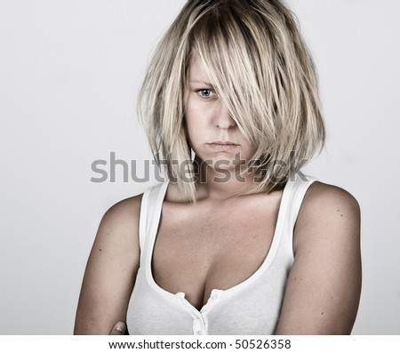 Powerful Shot of a Pensive Blonde Female in White Vest against Grey Background - stock photo