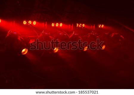 Powerful spotlights illuminate the scene with red light - stock photo