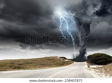 Powerful tornado and lightning above countryside road