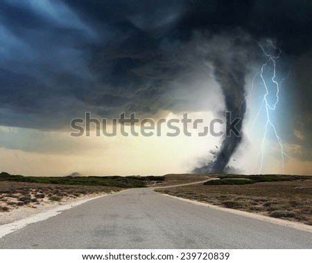 Powerful tornado and lightning above countryside road - stock photo