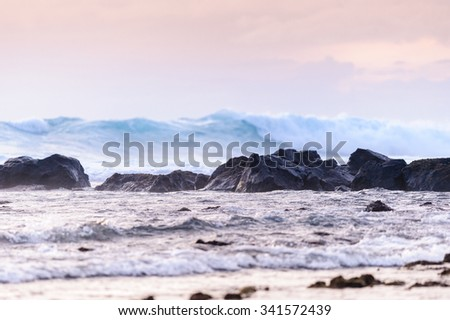 Powerful wave breaking along the rocky shore  - stock photo