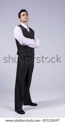 Powerful young businessman with his arms crossed (isolated on gray) - stock photo