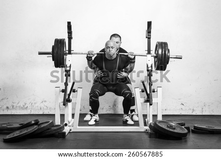 Powerlifter with strong arms lifting weights helped by his master - stock photo